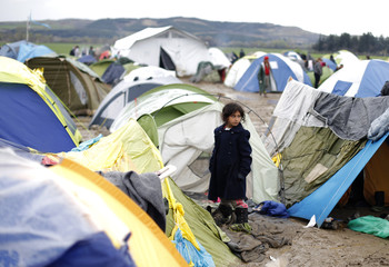 A migrant girl stands among tents at a makeshift camp on the Greek-Macedonian border near the village of Idomeni