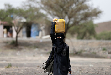 Woman carries a jerrycan she filled with water at a camp for internally displaced people near Sanaa