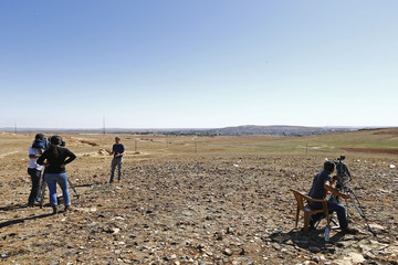 Members of the media watch the Syrian town of Kobani from a hill near the Mursitpinar border crossing, on the Turkish-Syrian border