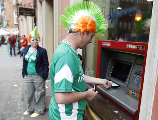 An Irish soccer fan withdraws money from a bank machine prior to a Euro 2012 soccer match between Spain and Ireland at the old town in Gdansk