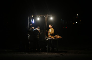 A Palestinian vendor fries chicken livers as people wait to buy in Gaza City