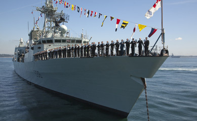 Sailors aboard HMCS Winnipeg raise their hats to Governor General Jean during Fleet Review in Victoria