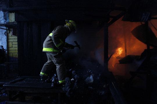 A firefighter holds an axe to break through wooden doors after a fire broke out at Comayaguela market in Tegucigalpa