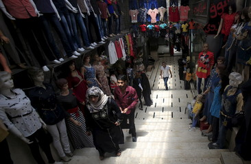 Palestinians shop in a market ahead of the Eid al-Fitr holiday marking the end of Ramadan in Nablus