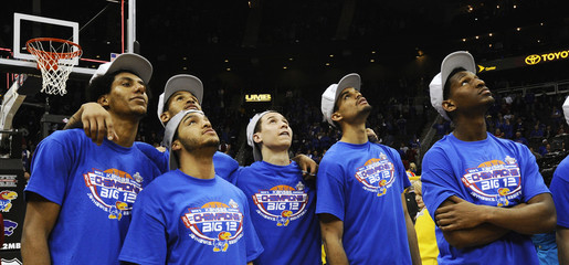 The Jayhawks watch a celebratory video after winning the NCAA men's Big 12 basketball tournament championship game in Kansas City, Missouri