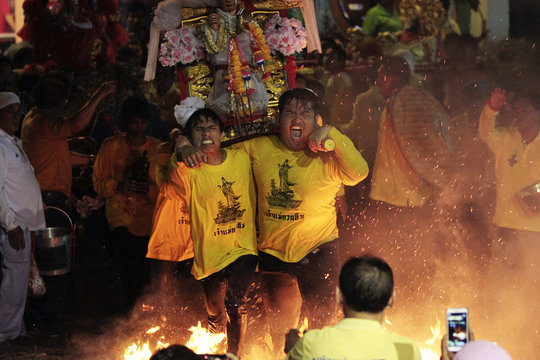 Devotees carry a wooden icon while walking through fire during the annual festival at Lim Ko Nieo temple in Thailand's southern province of Yala