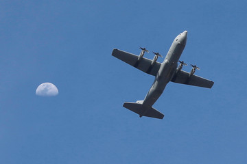 A plane is pictured as the moon is seen in the background, in Amman