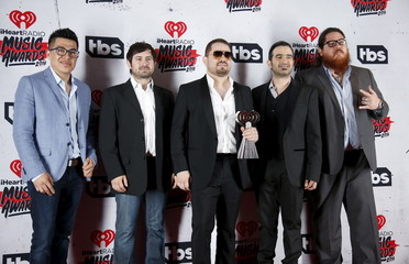 """Musical group Voz de Mando poses with their Regional Mexican Song of the Year award for """"Levantando Polvadera"""" backstage at the 2016 iHeartRadio Music Awards in Inglewood"""