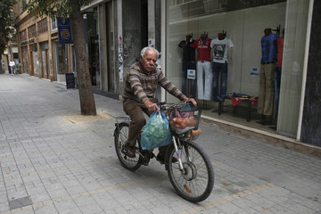 Man rides his bicycle carrying groceries in Nicosia