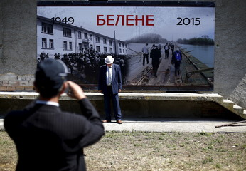 A man poses for a picture in front of a poster placed outside the crumbling building of a communist-era prison built on the site of former labour camp Belene, in Persin
