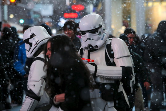 "Men dressed as Storm Trooper characters from ""Star Wars"" walk in Times Square as snow falls down during the first day of spring in New York"