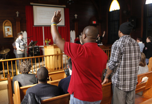 Members of the Open Door Community Fellowship Church listen and pray with Hitchcock at the Open Door Community Fellowship Church in Louisville