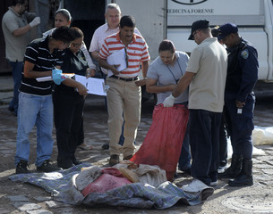 Forensic technicians look into bags containing dismembered parts of a human body in a neighborhood in Tegucigalpa
