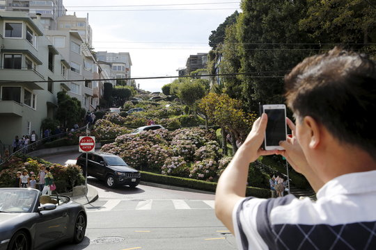 """A man snaps a photo of Lombard Street, a popular tourist spot also known as the world's """"crookedest street,"""" in San Francisco"""