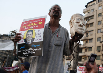 A man holds a self-made wood carving of Egypt's first Islamist president Mohamed Mursi and a poster, in Tahrir square