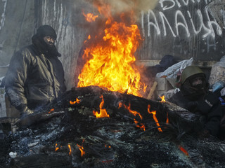 Anti-government protesters sit at an open fire as temperatures reach minus 20 degrees Celsius at a barricade near Independence Square in Kiev