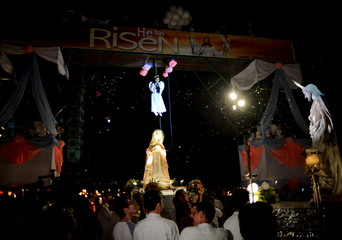 A girl portraying the role of an angel hangs from a platform during Easter Sunday celebrations in Manila