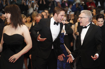 Cast members Binoche and Pattinson pose on the red carpet ahead of the screening of the film Cosmopolis by director Cronenberg in competition at the 65th Cannes Film Festival