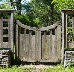 Distressed Grey Wood Gate with a Curved Top in Country Setting,  with Lichens  and Stacked Stone, Grass and Trees.