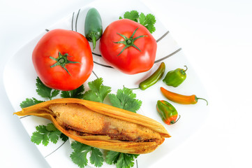 Mexican tamales made of corn and chicken with chiles and tomato isolated on white