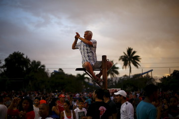A fan takes a photograph while sitting on a pole before a free outdoor concert by the Rolling Stones at the Ciudad Deportiva de la Habana sports complex in Havana