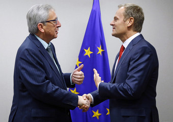 Newly nominated European Council President Tusk welcomes new European Commission President Juncker at the EU council headquarters in Brussels