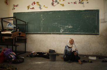 Palestinian woman, who fled her house that is adjacent to the border with Israel, stays at a United Nations-run school in Gaza City