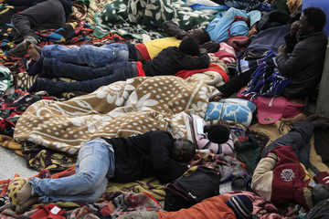 Ghanaians who fled the violence and unrest in Libya sleep on the ground at Djerba airport as they wait for a flight to return to their country