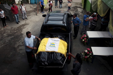 Relatives cover the bodies of Jason and Marielos Sanchez Mendez, the victims of a mudslide, with a flag, during a memoral in Santa Catarina Pinula