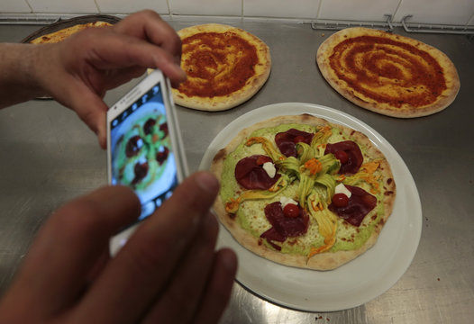 Jules Stassen, an unemployed Belgian, takes a photo of a pizza during a training at a French pizzaiolo school in Cap D'Ail
