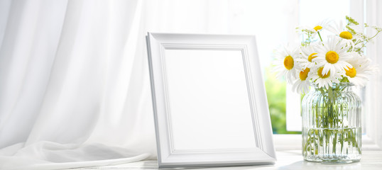 Picture frame near window with flower