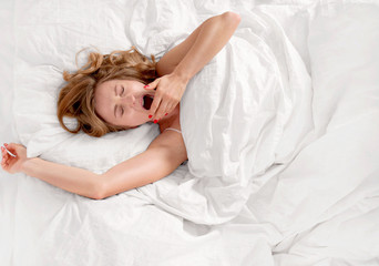 Woman waking up and yawning after sleep on bed.