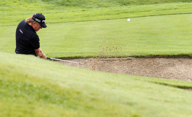 Jimenez hits out of the bunker onto the 9th green during the European Masters golf tournament in Crans-Montana