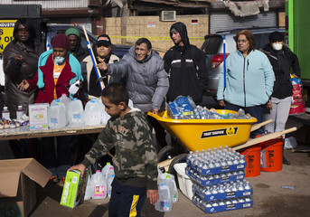 People wait for cleaning supplies and other donations in the Rockaways section of the Queens borough of New York