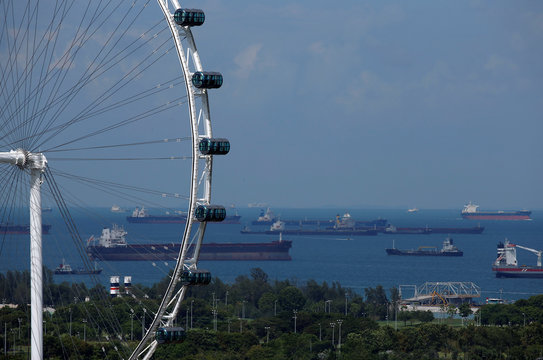 Tankers line the anchorage area behind the Singapore Flyer observatory wheel in Singapore