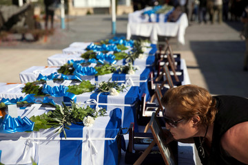 A woman kisses a framed picture in front of caskets of soldiers draped in the Greek and Cypriot flags, whose remains were recently discovered in the wreckage of a Greek military aircraft shot down by friendly fire in 1974, at the Tymvos Macedonitissas mili