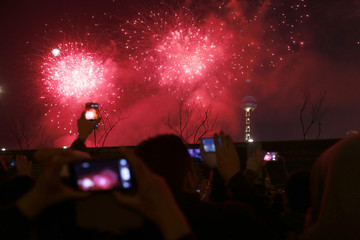 Visitors take pictures and videos as fireworks explode over Oriental Pearl Tower as part of a New Year countdown celebration on the Bund in Shanghai