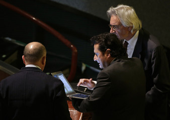 Captain of the Costa Concordia cruise liner Schettino holds a laptop as he stands between his lawyers Pepe and Laino during his trial in Grosseto