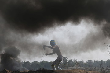 Palestinian protester uses a sling to hurl stones at Israeli troops during clashes near border between Israel and Central Gaza Strip