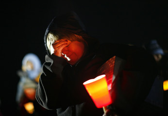 A woman cries during a candlelight vigil in Newtown