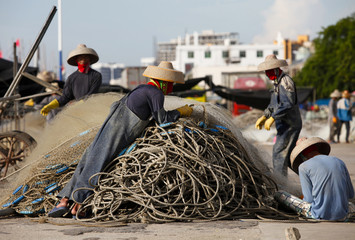 Boat crew repair fishing nets at a port in the city of Dongfang on the western side of China's palm-fringed island province of Hainan