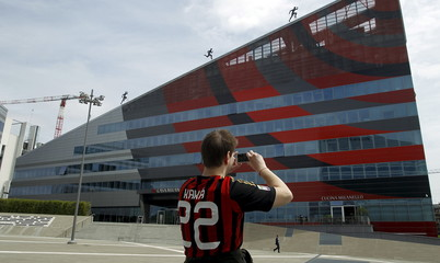 An AC Milan's supporter takes a picture of the AC Milan flagship store and museum in Milan