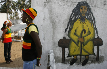 A member of the Rastafari movement stands beside a drawing of a Rasta man as she awaits the arrival of Ivorian officials in the Rasta village of Port Bouet