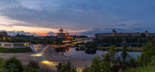 Opposition of two medieval fortresses on the river Narva at sunset, Estonia and Russia border. Wide panoramic view