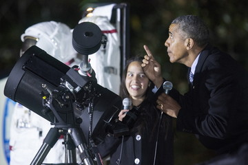 U.S. President Barack Obama points at the moon after looking at it through a telescope with Agatha Sofia Alvarez-Bareiro, a high school senior from Brooklyn, New York, during White House Astronomy Night