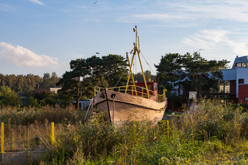 An old boat staying in reed bog near sea at sunset. Rustic decoration in fishing village, Estonia.