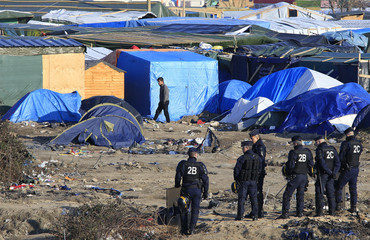 """French police officers secure the area during operations to clear dismantled shelters of the camp known as the """"Jungle"""" in Calais"""