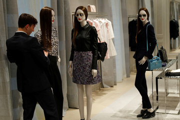 A shop assistant adjusts a mannequin at Dior's new flagship store in London