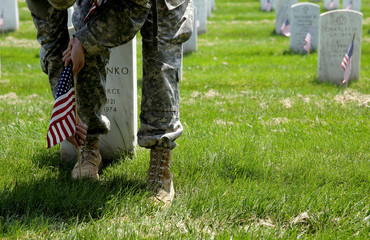 A soldier places flags in front of the graves at Arlington National Cemetery in Washington.