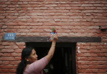 "A woman sticks a picture of a snake god and offers prayer to it at the main entrance of her house, to mark the ""Nag Panchami"" festival in Kathmandu"